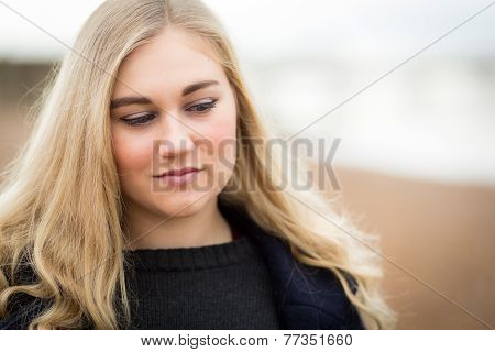 Young Blond Teenage Girl Thinking On The Beach