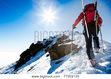 Mountaineer walking up along a snowy ridge with the skis in the backpack. In background a shiny bright sun. Concepts: adventure, courage, determination, self-realization, dangerous, extreme sport.