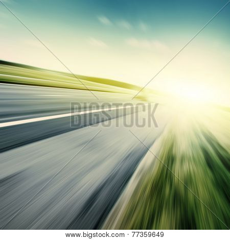 Country asphalt road in motion blur at sunset.
