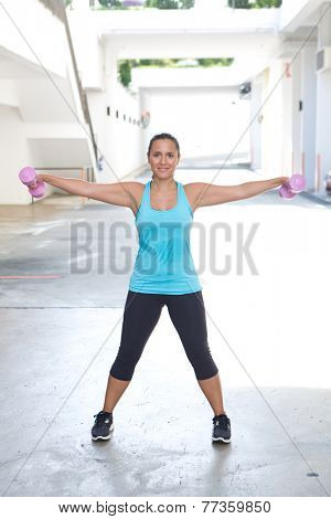 Beautiful sporty hispanic woman in blue  lifting pink dumbbell stretching both arms out for bicep building, outdoors