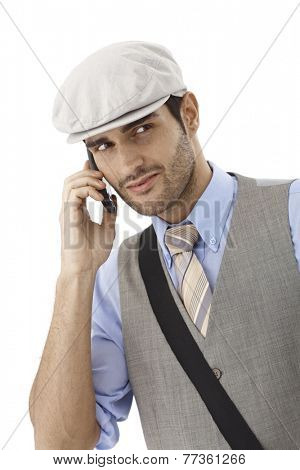 Young man talking on mobilephone, looking away, wearing hat.