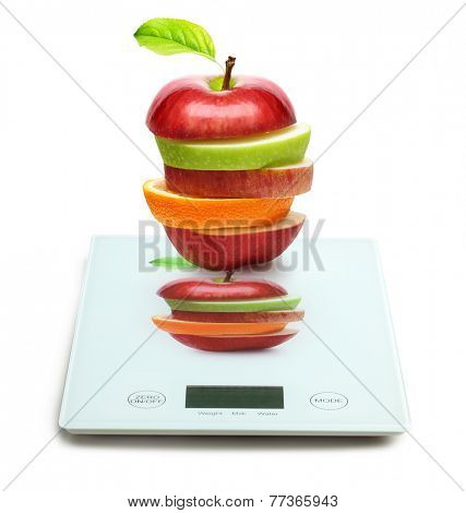Apples and orange fruit on digital weight scale