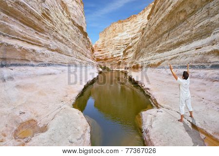 Gorge Ein-Avdat in desert Negev, Israel. The slender elderly woman in a white suit for yoga carries out an asana