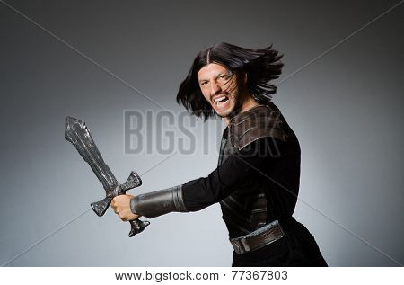 Angry knight with sword against dark background