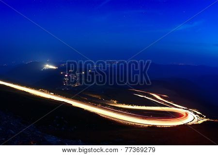 Landscape from the rocky Fagaras mountains in Romania in the summer evening with Transalpina winding road in the distance