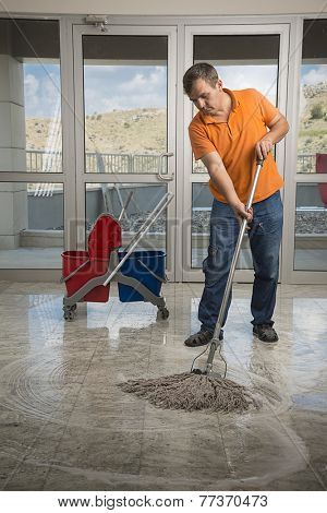 Male cleaner with mop and uniform cleaning hall floor.