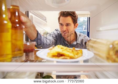Man Looking Inside Fridge Full Of Unhealthy Food