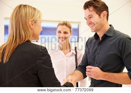 Estate Agent Shaking Hands With Clients In Empty Office