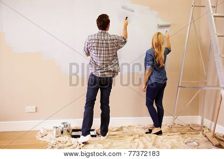 Couple Decorating Room Using Paint Rollers On Wall