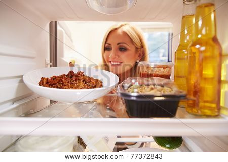 Woman Taking Plate Of Leftover Food From The Fridge