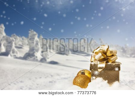 Golden gift box and Christmas decorations in the snow, snow cowered pine trees in the background