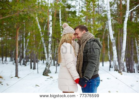 Young amorous couple standing face to face and laughing
