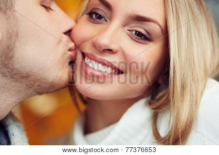 Amorous man kissing his sweetheart on cheek