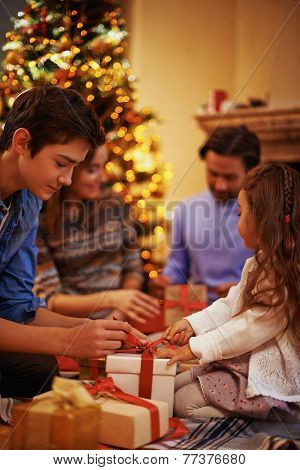 Youthful guy and cute little girl untying ribbon of giftbox
