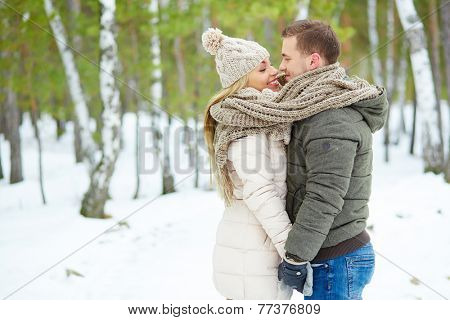 Young amorous couple standing face to face and looking at one another