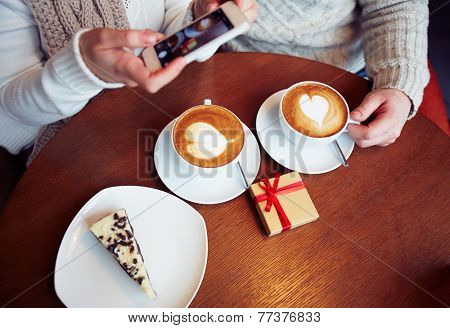 Two cups of cappuccino, cheesecake and small giftbox on table in cafe