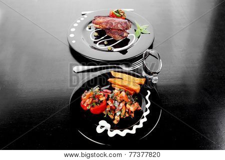 fresh red beef meat steak barbecue garnished vegetable salad sweet potato and basil on black plate over black wooden table with bbq sauce in sauceboat