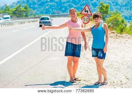 Two Friends Hitchhiking Summer In The Mountains