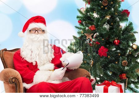christmas, holidays and people concept - man in costume of santa claus with notepad, pen and christmas tree sitting in armchair over blue lights background