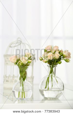 Beautiful bouquet of flowers in vases on window background
