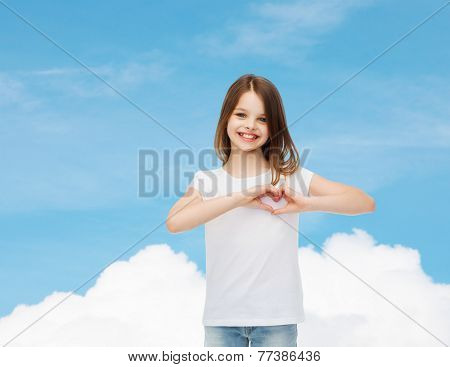 advertising, charity, childhood and people - smiling little girl in white blank t-shirt making heart-shape gesture over blue sky background