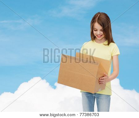 advertising, childhood, delivery, mail and people - smiling little girl holding open cardboard box and looking into it over blue background