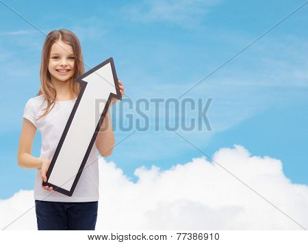 advertising, direction, air, aviation, and childhood concept - smiling little girl with white blank arrow pointing up over blue sky background