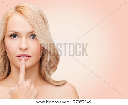 health, people and beauty concept - beautiful young woman touching her lips over pink background