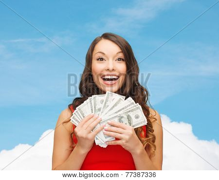 sale, winning, banking and people concept - smiling woman in red dress with us dollar money over blue sky and white cloud background