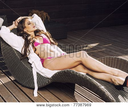 beauty young woman after spa in bikini and robe at hotel resort, on terrace enjoying sun