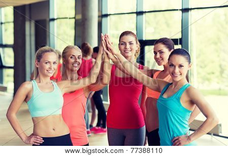 fitness, sport, friendship and lifestyle concept - group of women making high five gesture in gym