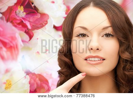 beauty, people and health concept - beautiful young woman pointing finger to her chin over pink floral background