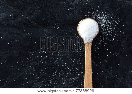 sugar in wooden spoon on black background