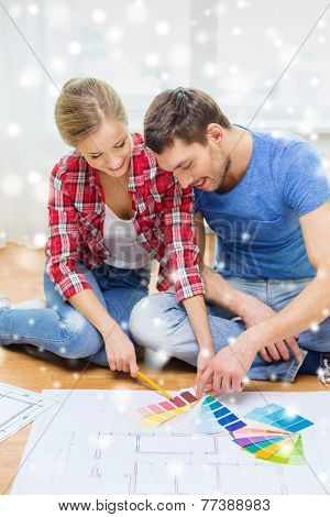 repair, interior design, building, renovation and people concept - smiling couple selecting color from samples at home