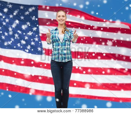 patriotism, education, gesture and people concept - smiling girl in casual clothes showing thumbs up over american flag and blue sky with snow background