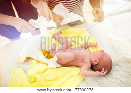 Parents changing baby nappy