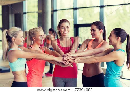 fitness, sport, friendship and lifestyle concept - group of women with hands on top of each other in gym