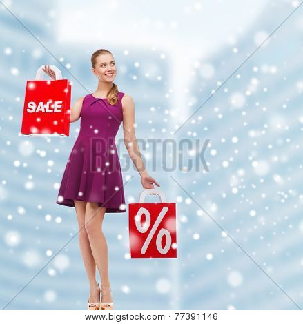 sale, gifts, christmas, holidays and people concept - smiling woman in purple dress holding shopping bags with percentage sign over mall background