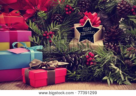 a pile of gifts and a natural christmas wreath with pine cones and red berries, and a star-shaped signboard with the text merry christmas written in it