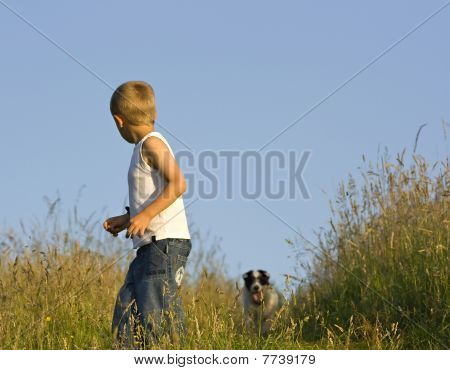 An Outdoor Portrait Of A Cute Seven Year Old Boy With His Dog