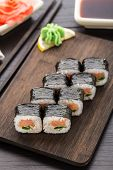 stock photo of scallion  - Sushi rolls with salmon and scallion on a wooden board  - JPG