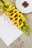 image of gladiolus  - chocolate heart on a plate yellow gladioluses and a blank sheet of paper for inscription on the wooden background - JPG