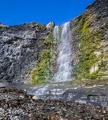 pic of tide  - A waterfall cascades to the bottom of a cliff at low tide - JPG