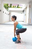picture of kettlebell  - Beautiful sporty hispanic woman in blue attire holding a blue kettlebell in dead lift post outdoors - JPG
