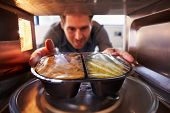 stock photo of oven  - Man Putting TV Dinner Into Microwave Oven To Cook - JPG