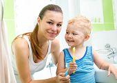 foto of bathtime  - smiling mother and kid son brushing teeth in bathroom - JPG