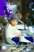 stock photo of knitted cap  - the girl in lilac jeans in a knitted cap and with a knitted scarf sits on a sledge near a Christmas fir - JPG