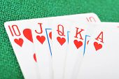 stock photo of over counter  - Poker winning hand over a vivid green background - JPG