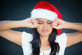 image of spoiled brat  - Closeup portrait cute christmas woman in red santa claus hat white dress putting hands up to face about to cry isolated gray black background - JPG