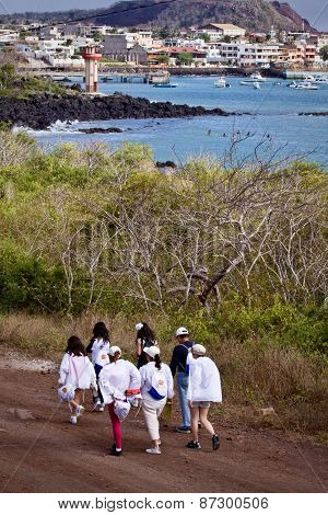 Group of unidentified tourists hiking along San Cristobal Island in Galapagos